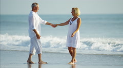 Happy Caucasian seniors in white clothing dancing together on the beach Stock Footage
