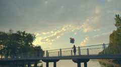 Woman with colorful balloons jumping on the bridge of happiness showing Stock Footage