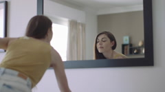 Young adult female looking at reflection in mirror - stock footage