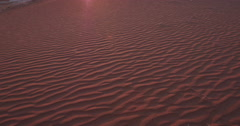 4K panning shot of sand dunes of the sun setting in the background  Stock Footage