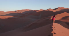 4K panning shot of male tourist admiring the view of endless sand dunes of the Stock Footage