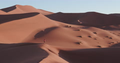 4K static shot of male tourist walking on the sand dunes inside the Stock Footage