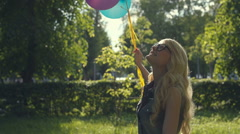Happy young woman with colorful latex balloons, gleefully jumping for joy in a Stock Footage