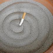 smoked cigarettes in sand ashtray - stock photo