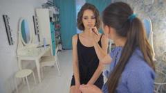 Beauty makeup artist woman applying make up sensual brunette girl Stock Footage