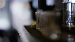 4K Close up of barman pouring alcohol into row of shot glasses - stock footage