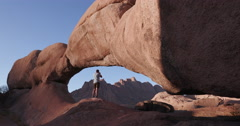 4K male tourist standing inside the famous arch of the Spitzkoppe mountains and Stock Footage