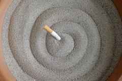 smoked cigarettes in sand ashtray - stock photo