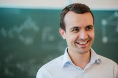 Portrait of young happy smiling teacher or student man standing near chalkboard Stock Photos