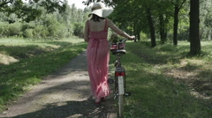 Beautiful girl goes by Bicycle on the street holding the bike back from the Park Stock Footage