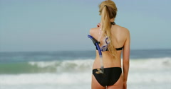 Attractive woman in bikini hanging out on psychedlic beach Stock Footage