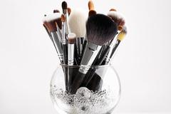 Makeup brushes in a glass vase with crystals - stock photo