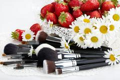 Set of makeup brushes with strawberries and flowers Stock Photos