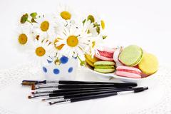 Set of makeup brushes with flowers and macaroons Stock Photos
