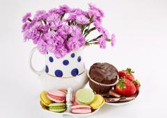 Flowers in vase with macaroons on saucer. Carnations and sweets. Stock Photos