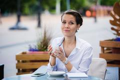 Lovely business woman with smile is sitting with touch pad in comfortable Stock Photos
