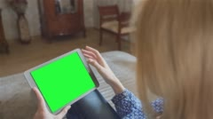 Beautiful girl using tablet pc with pre-keyed green screen sitting on sofa - stock footage