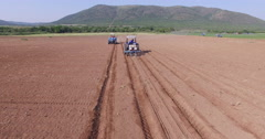 4K aerial view of tractors ploughing fields Stock Footage