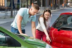 Young Woman Showing Man Car Collision At Roadside - stock photo