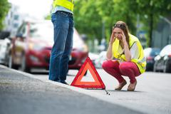 Young Worried Woman Crouching Near Triangular Warning Sign With Broken Down C - stock photo