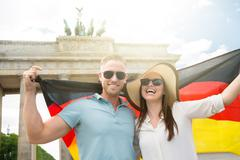 Smiling Young Couple Holding Flag At Brandenburg Gate - stock photo