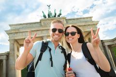 Happy Couple Making Peace Sign In Front Of Brandenburg Gate - stock photo