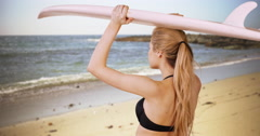 Pretty white girl waiting to catch the perfect ride while holding surfboard Stock Footage