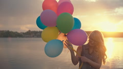Positive emotions, happy girl with multicolored balloons enjoying summer beach Stock Footage