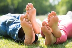 Close-up Of Couple Feet While Lying On Grass At Park - stock photo