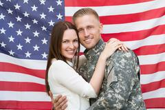 Portrait Of Young Male Soldier With His Wife In Front Of American Flag Stock Photos