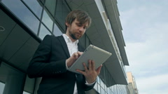 Handsome young man with tablet in the streets near office - stock footage
