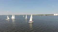 Sailing yacht with white sails floating on the river on background of the city Stock Footage