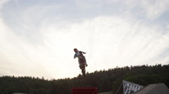 Extreme Freestyle Motocross Jumping over camera at dusk Stock Footage