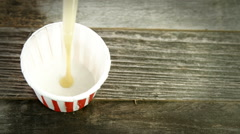 Pouring Mustard into paper portion cup, slightly elevated angle. Stock Footage
