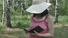 Young girl in hat in the Park reading a book, the Steadicam, slow motion camera Stock Footage