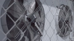 Air conditioning unit with two rotating fans on the wall of the building - stock footage
