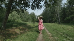 Rear view of young woman with hat running on the meadow, slow motion Stock Footage