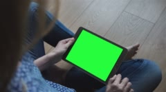 Beautiful girl using tablet with pre-keyed green screen sitting on the floor - stock footage