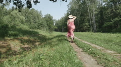 Rear view of young woman in hat running along the path, slow motion - stock footage