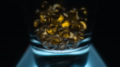 In a glass beaker fall transparent yellow balls of fish oil. Slow mo, slo mo Stock Footage