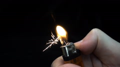 Ignite a cigarette lighter in the hand on black background. Slow mo, slo mo Stock Footage