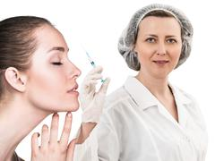 Beautiful woman face near doctor with syringe - stock photo