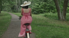 Young woman in summer dress and hat riding a Bicycle through the Park, slow Stock Footage