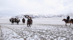 GOLDEN EAGLE HUNTER FESTIVAL HORSEMAN GALLOPING SNOW Stock Footage