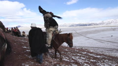 GOLDEN EAGLE HUNTER FESTIVAL HORSEMAN SNOW MOUNTAINS Stock Footage