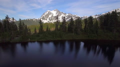 Scenic Aerial Pan Across Forest Lake with Snowy Mountain Peak Background Stock Footage