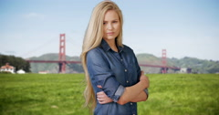 Beautiful young blond woman standing in front of golden gate bridge Stock Footage