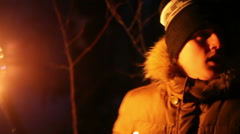 Scared young man looks around with the torch at night in the winter forest Stock Footage