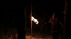 Young man goes through the snowy winter forest at night with the torch Stock Footage