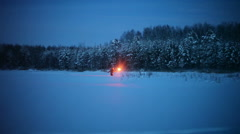 A young guy with the torch goes through the snow-covered field at night Stock Footage